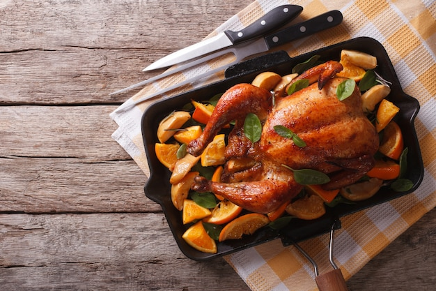 Roasted chicken with apples and oranges in a pan
