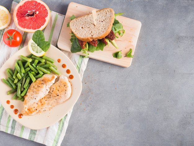 Roasted chicken with green beans and sandwich on table