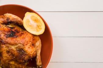 Roasted chicken with lemon on orange plate