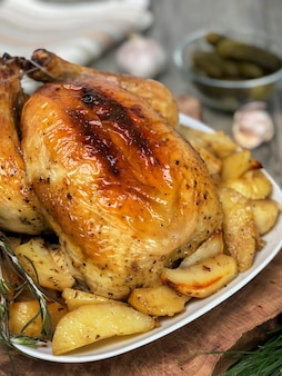Roasted chicken with potatoes on wooden table.