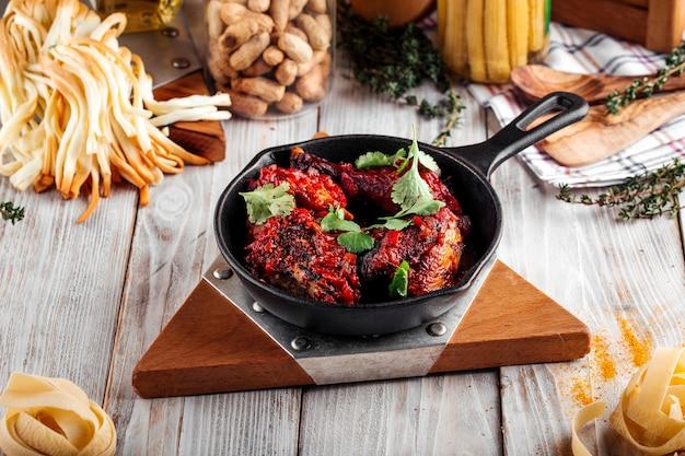 나무 장식 테이블에 주철 팬에 붉은 소스를 곁들인 구운 치킨