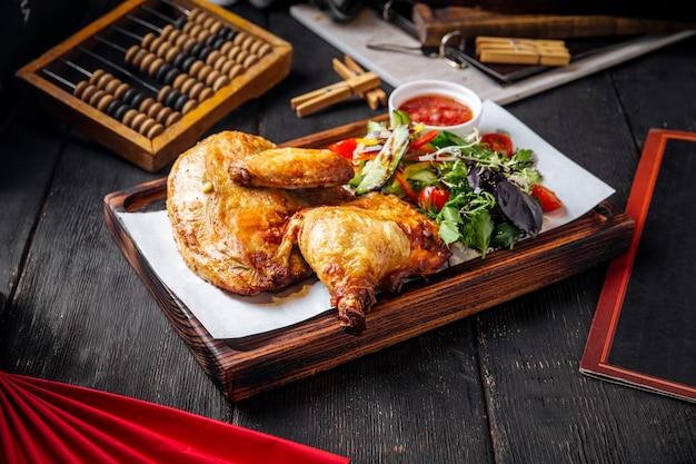 Жареный цыпленок с соусом и зеленью на деревянной доске
