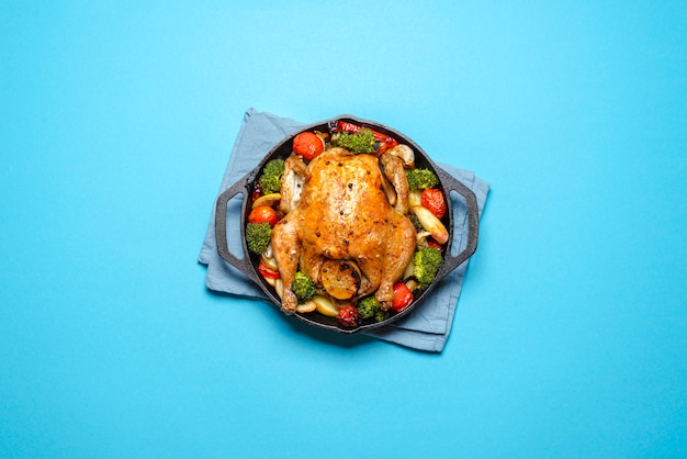 Roasted chicken with vegetables in an iron cast