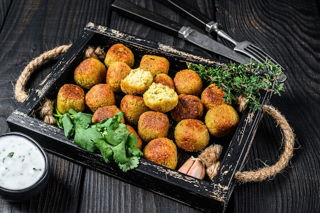 Roasted chickpeas falafel balls with garlic yogurt sauce in a wooden tray