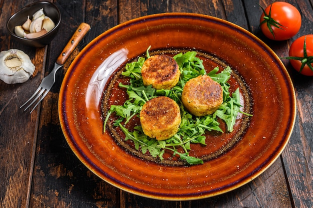 ひよこ豆のファラフェルパテのロースト、ルッコラのプレート。暗い木製のテーブル。上面図。