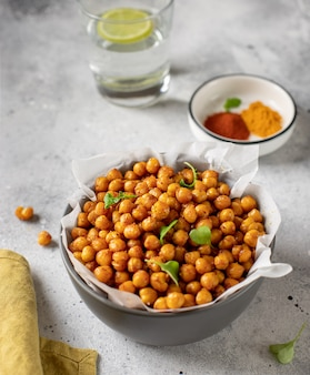 Roasted chickpeas with spices in bowl healthy food concept gray concrete surface,
