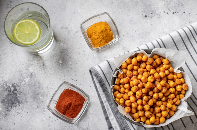 Roasted chickpeas with various spices in a bowl clean eating, trendy food gray stone surface,