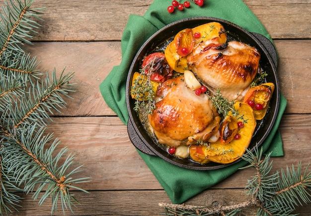 クリスマスディナーにカボチャを添えたローストクリスマスチキン太もも。お祝いの装飾が施された木製のテーブル