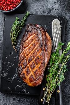 ローストしたクリスマスアヒルの胸肉フィレステーキ。黒の背景。上面図。