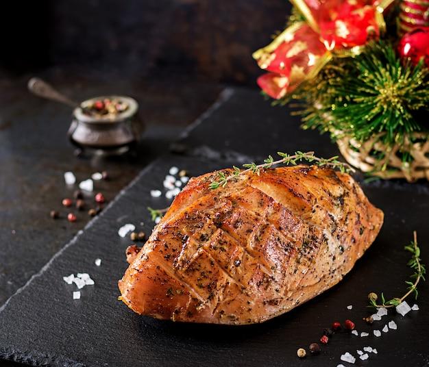 Roasted christmas ham of turkey on dark rustic table.  festival food.