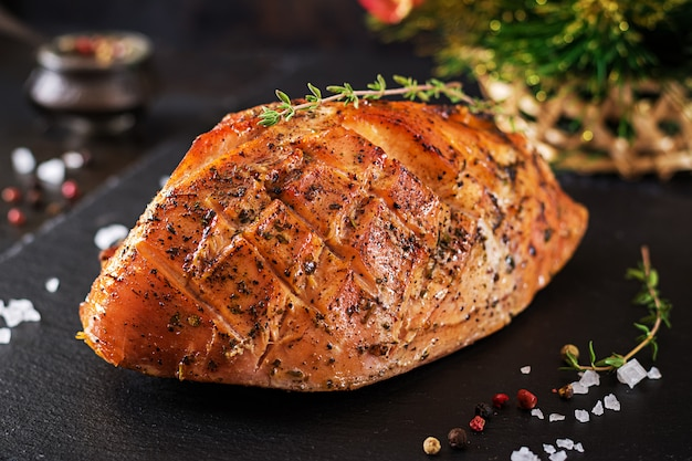 Roasted christmas ham of turkey on dark rustic table.  festival food.