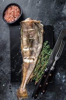 Жареная белая рыба трески с тимьяном на мраморной доске. вид сверху.