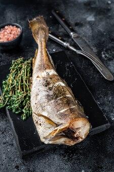 Белая рыба треска жареная с тимьяном на мраморной доске