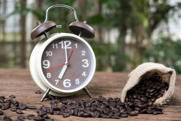 Roasted coffee bean and alarm clock on wooden floor in nature for mylti purposes