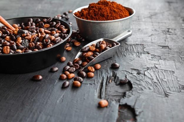 黒い木製のテーブルの上の焙煎コーヒー豆とコーヒー粉
