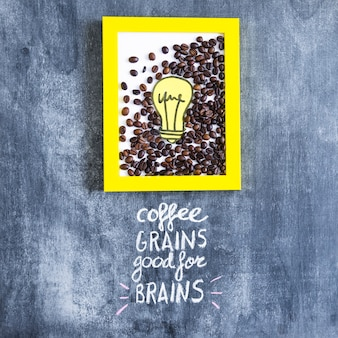 Roasted coffee beans and paper cutout light bulb frame with text on chalkboard