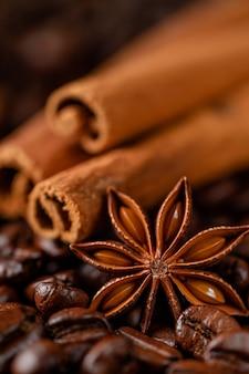 Жареный кофе в зернах и фон специй. макросъемка, вертикальная