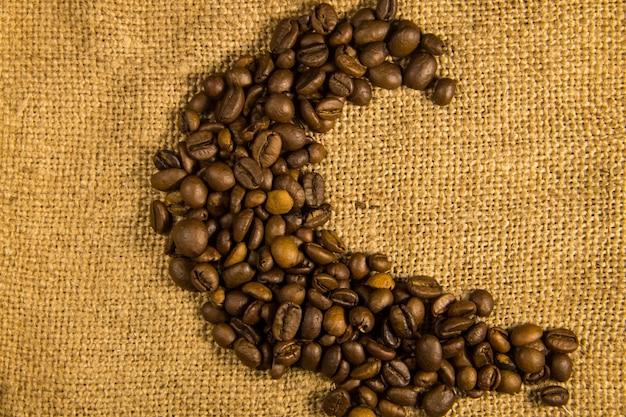 荒布織りの背景に月の形に配置された焙煎コーヒー豆