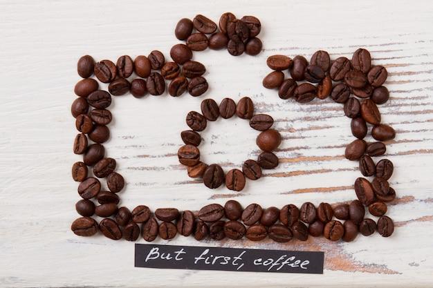 볶은 커피 콩을 사진 카메라 모양으로 배열. 표면에 흰색 나무입니다. 하지만 먼저 커피.