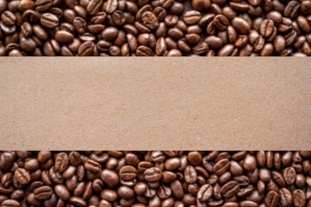 Фон жареных кофейных зерен с пустой коричневой бумагой для производственной этикетки