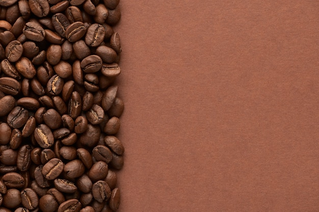 Roasted coffee beans on brown background with copy space close up top view high quality photo