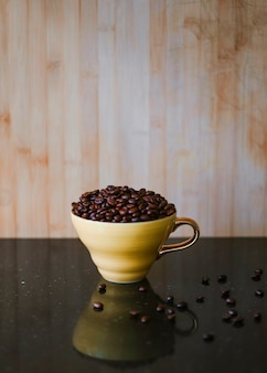 Roasted coffee beans in brown ceramic cup on reflective desk