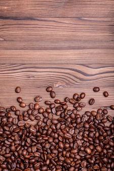 Roasted coffee beans on a brown wooden background with copyspace.