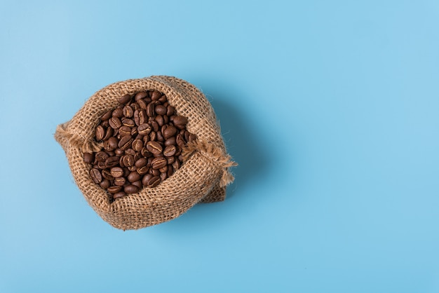 Roasted coffee beans in burlap, top view