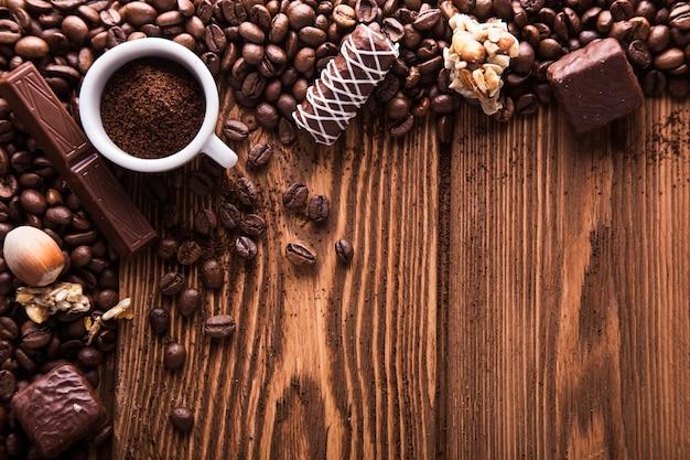 焙煎したコーヒー豆、チョコレート、キャンディー、ナッツ、木の表面に挽いたコーヒーを入れたカップ