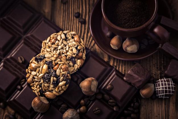 コーヒー豆のロースト、チョコレート、ミューズリー、キャンディー、ナッツ、木の表面にカップ