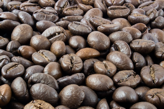 Roasted coffee beans, coffee beans text background in full focus.