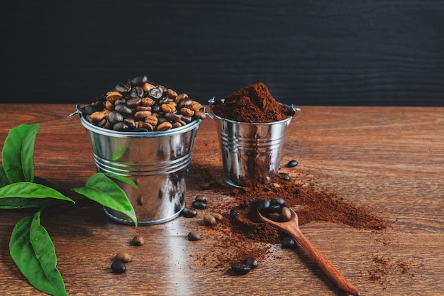 Roasted coffee beans and coffee powder on a wooden table