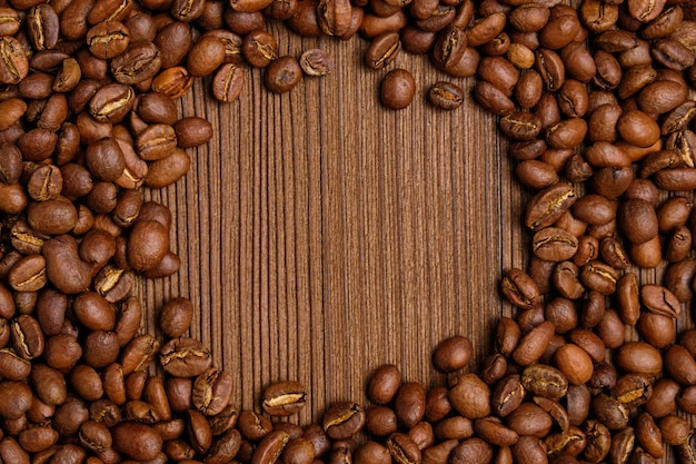 Roasted coffee beans create a circle for copy space on the background of burnt wooden background.