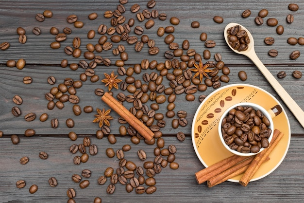 Roasted coffee beans in cup and wooden spoon. cinnamon sticks on saucer. coffee beans and star anise on table. dark wood background. flat lay