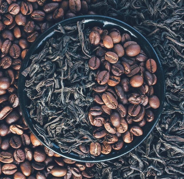 Roasted coffee beans and dry leaves of black tea, top view close-up