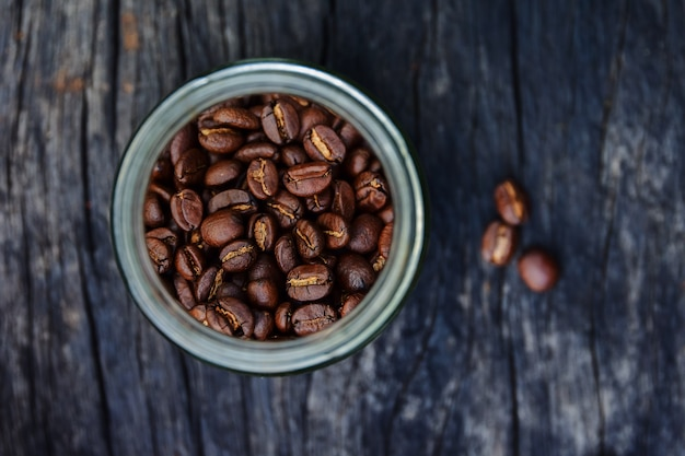 Roasted coffee beans in glass containers on old wood table, overhead view with copy space