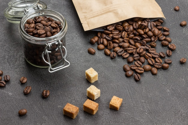 Roasted coffee beans in glass jar and in paper bag. pieces of brown sugar on table. top view.