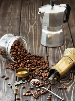 Roasted coffee beans in a glass jar, scattered on a wooden brown table