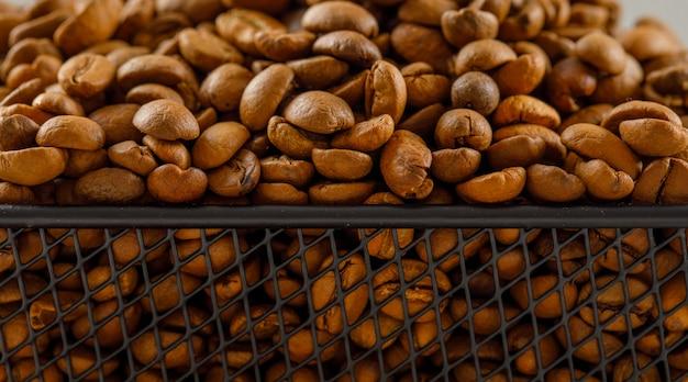 약간 흰색 표면에 검은 바구니에 볶은 커피 콩. 측면보기.