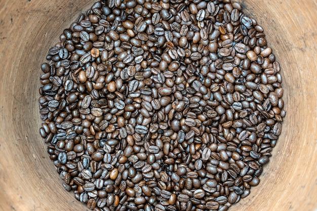 인도네시아 발리 현지 시장의 진흙 냄비에 볶은 커피 콩. 클로즈업, 평면도