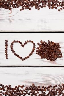 Жареные кофейные зерна в форме буквы i и сердца. куча кофейных зерен на белой древесине. я люблю концепцию кофе.