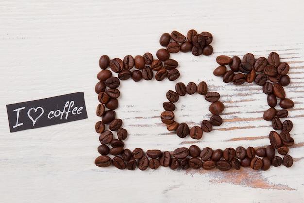 사진 카메라 모양의 볶은 커피 콩. 커피 개념에 대한 사랑. 흰색 목재 표면.