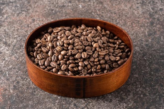 暗い背景に木製の箱でコーヒー豆の焙煎。