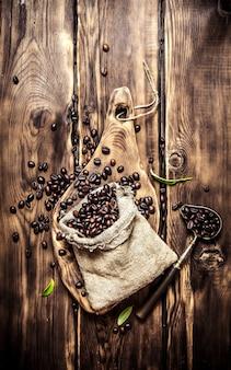 오래 된 가방에 볶은 커피 콩. 나무 배경.