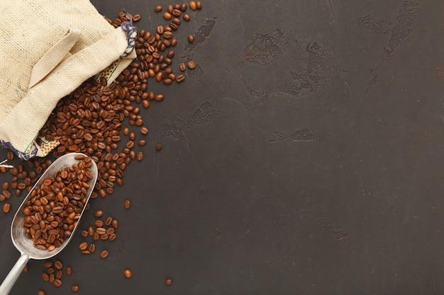 黄麻布の袋に入れて焙煎したコーヒー豆と、コピースペースのある灰色のテクスチャ背景に古いスクープ。コーヒーショップ広告のミニマルなデザイン、上面図