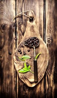 木の板に古いスプーンで焙煎したコーヒー豆。木製の背景に。