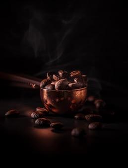 어두운 배경에 연기와 함께 구리 숟가락에 볶은 커피 콩. 커피의 향기를 인식하는 개념.