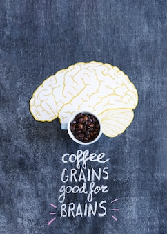 Roasted coffee beans in the mug on the paper cutout brain with text on blackboard