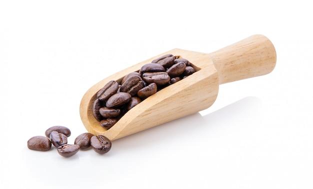 白い壁に木製のスクープでローストコーヒー豆