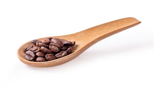 白い壁に木のスプーンでローストコーヒー豆